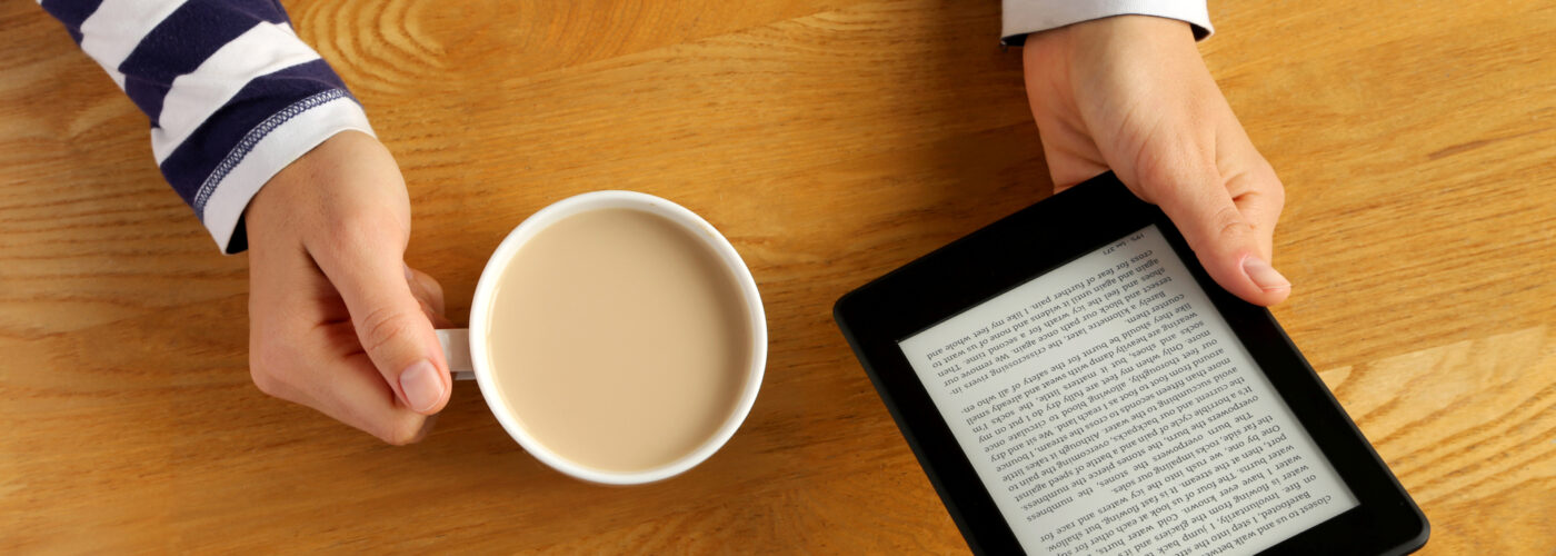 Kindle book on table with cup of coffee.