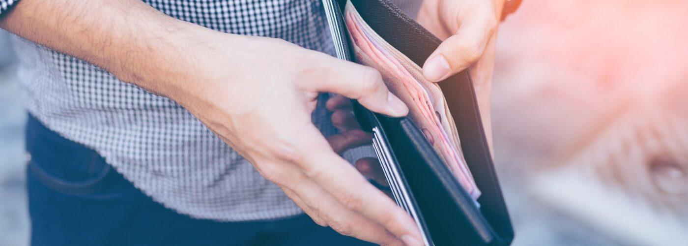 Man standing holding black wallet full of money.