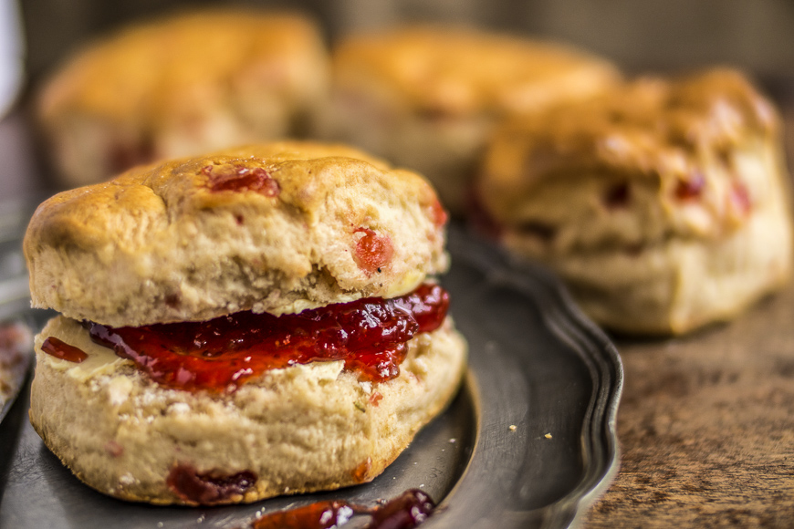 Cherry Scone with strawberry jam. in close up. Out of focus scones in the background.