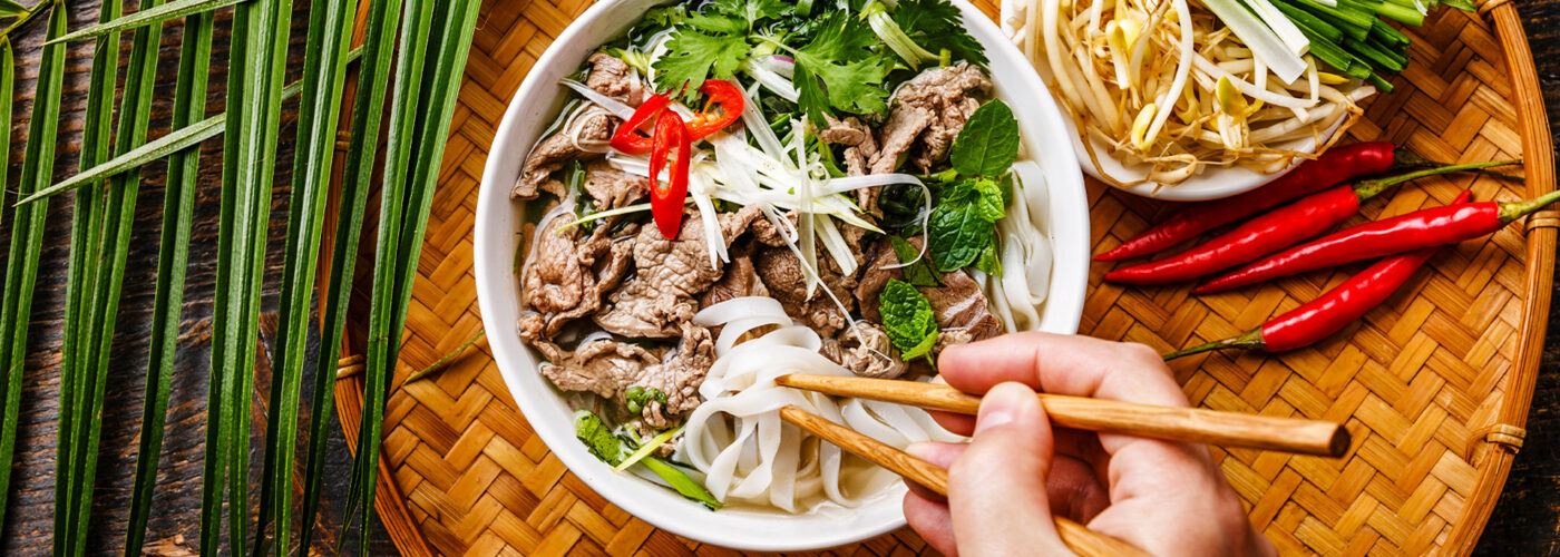 Pho Bo vietnamese Soup with beef and chopsticks in male hand