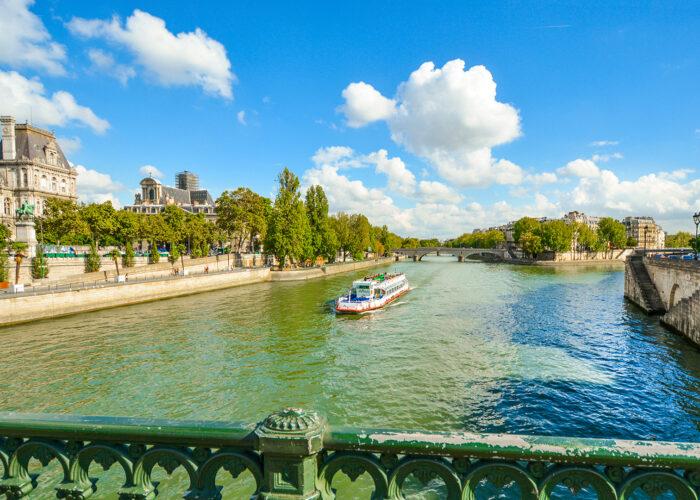 A cruise tourist boat floats down the Seine River near the Ile de la Cite in Paris, France