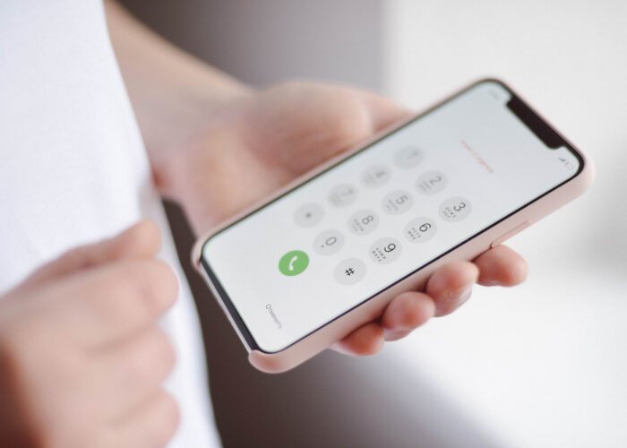 hand holding phone with dial buttons.