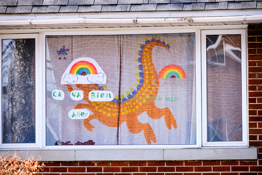 "House window with rainbow drawings and slogan ""Ca va bien Aller"" as message of hope in Montreal part of ""It's going to be OK"" movement during CoVID19 epidemic"