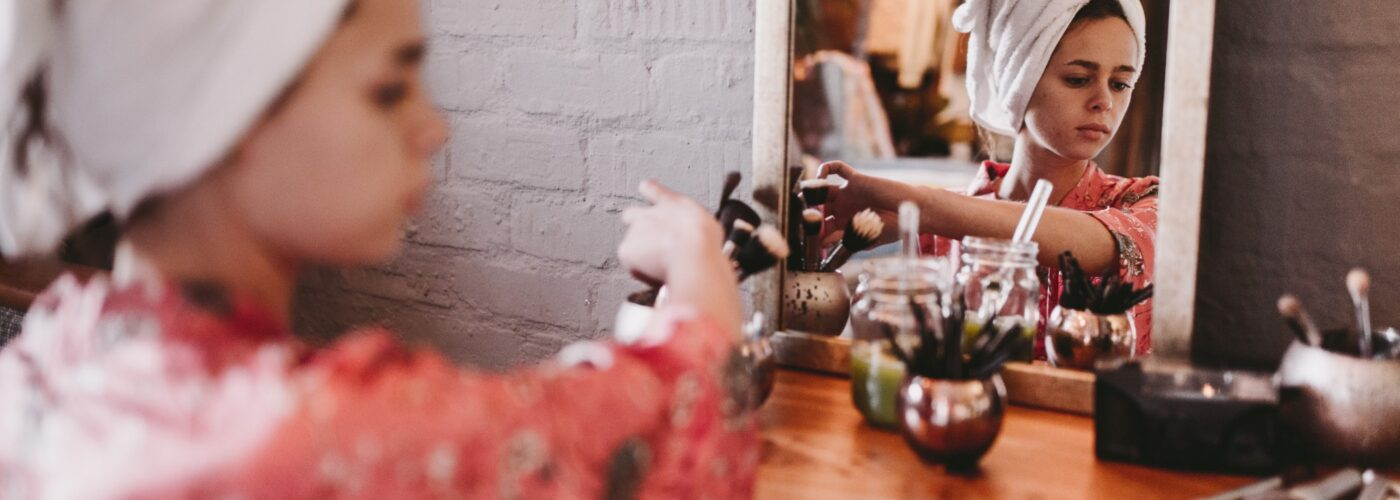 woman putting on makeup at mirror