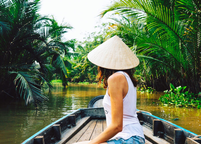 A young woman in a Vietnamese hat rides a boat on the Mekong River in Vietnam.The girl is traveling in a boat along the Mekong Delta in Vietnam.A serene river tour on the Mekong Delta, Can Tho Vietnam