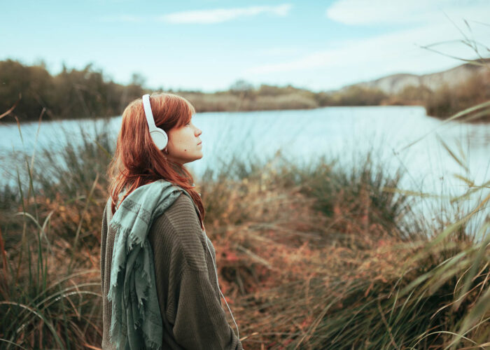 woman with headphones at lake.