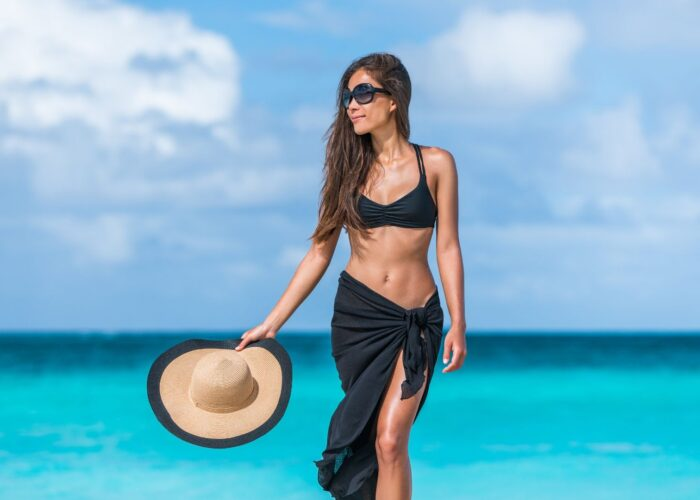 woman in bikini with cover-up and hat on beach.