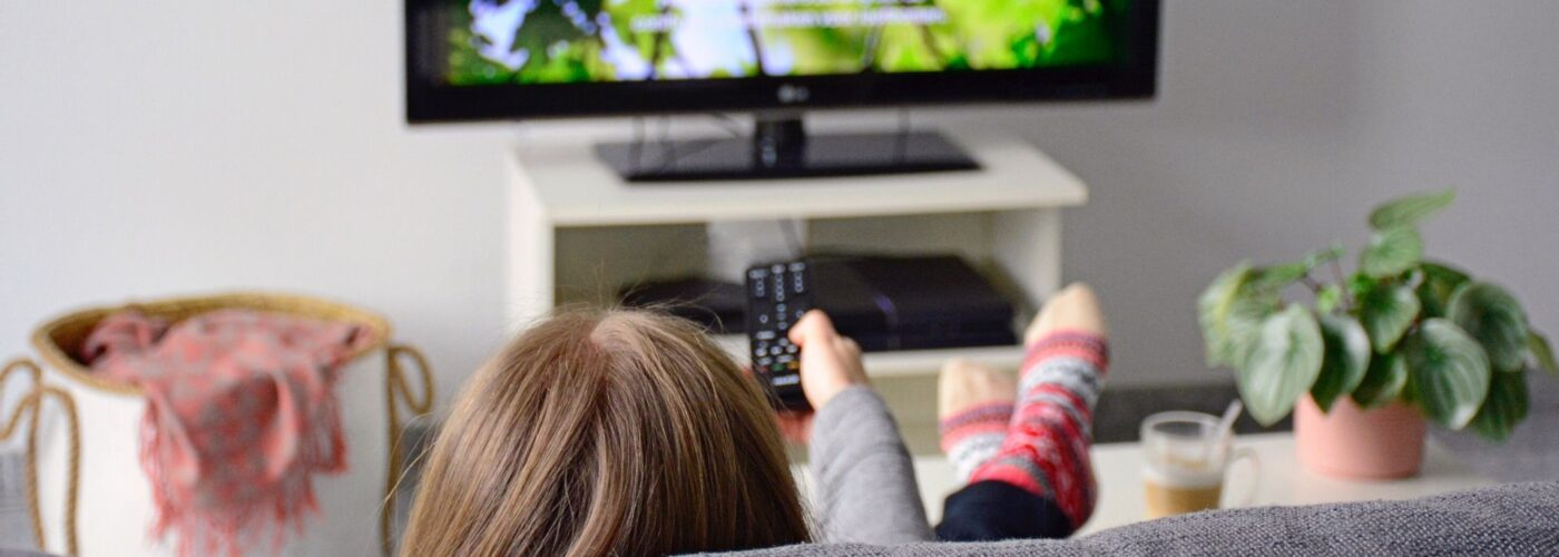 woman with remote control watching tv on couch.