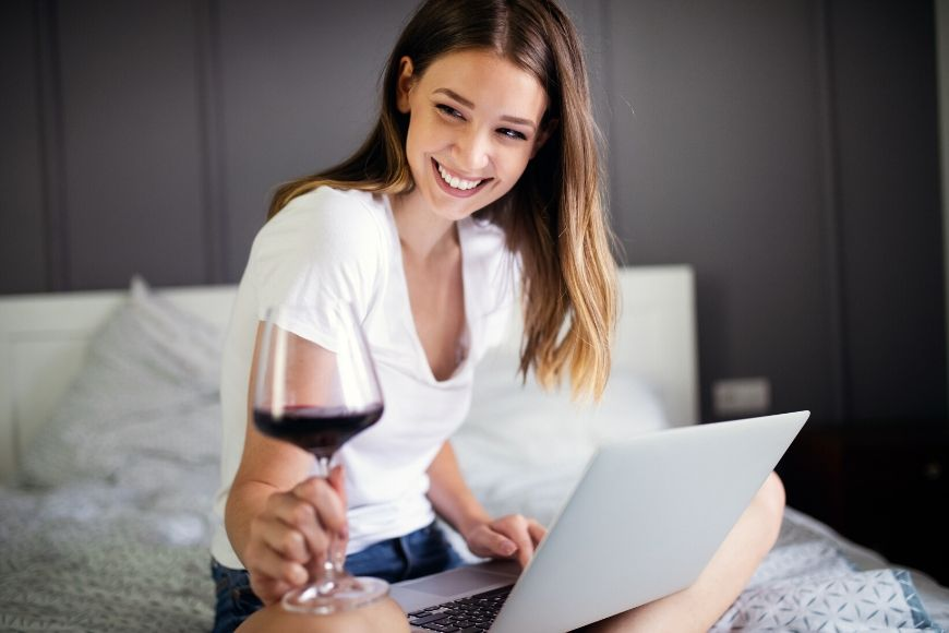 young woman with wine on laptop at home.