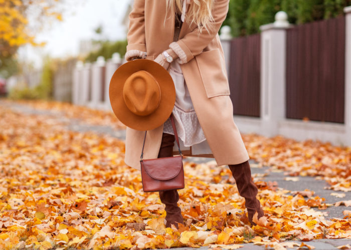 Woman dressed in warm autumn clothes on a street covered with fallen orange leaves