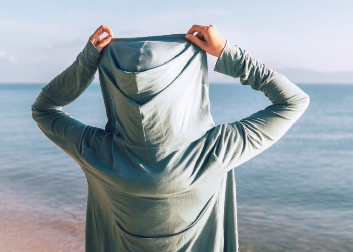 Person wearing a hoodie at the beach