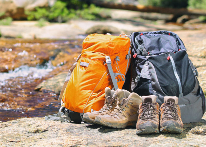 Two backpacks and some boots by a stream in nature