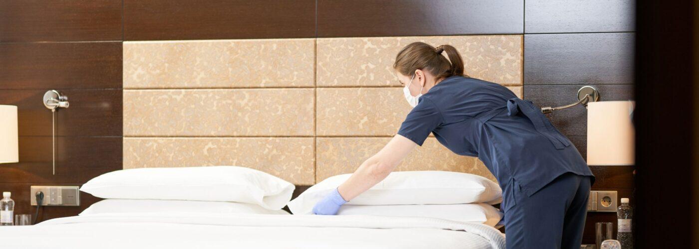 Housekeeper wearing a mask in hotel room.