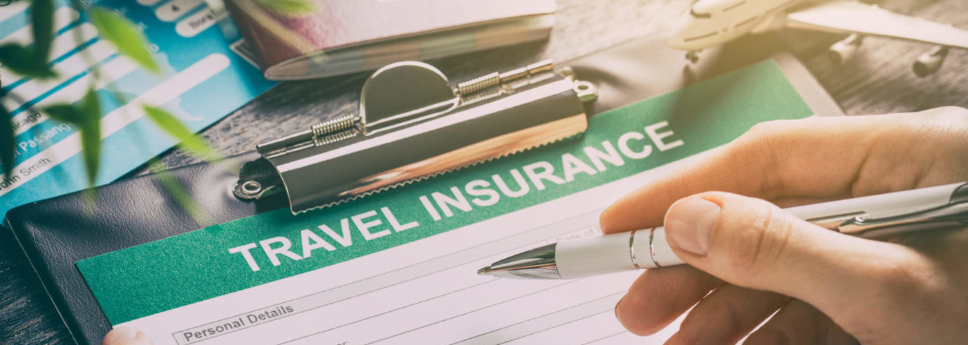 Person filling out travel insurance forms on decorated table
