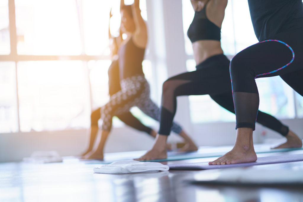 People doing yoga in a sunny room