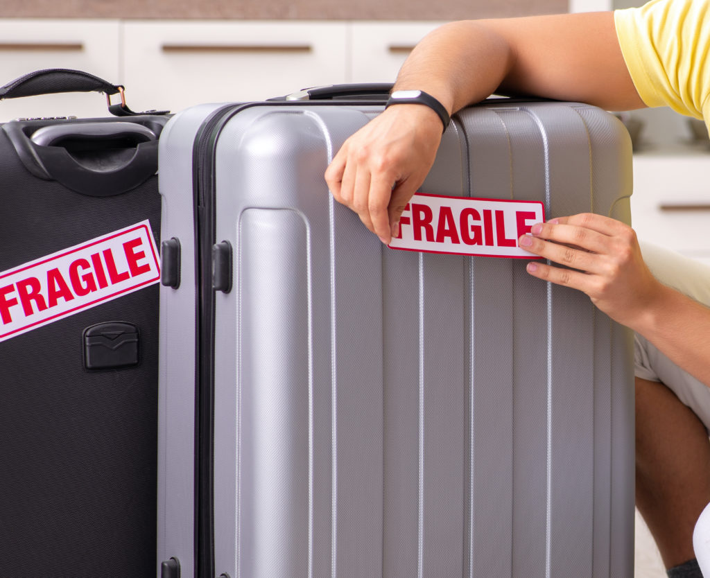"""Man placing """"Fragile"""" stickers on his suitcases"""