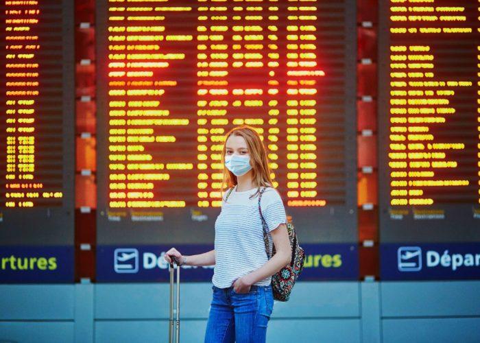 woman at airport wearing mask.