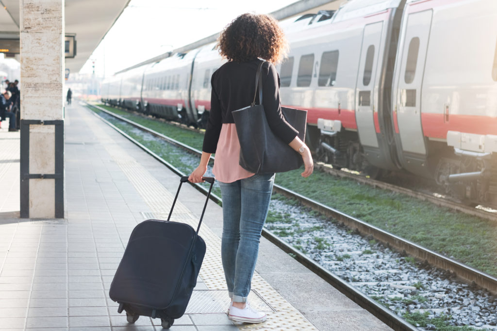 Woman waits for train with luggage