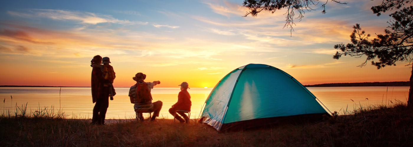 Family of four camping at sunset