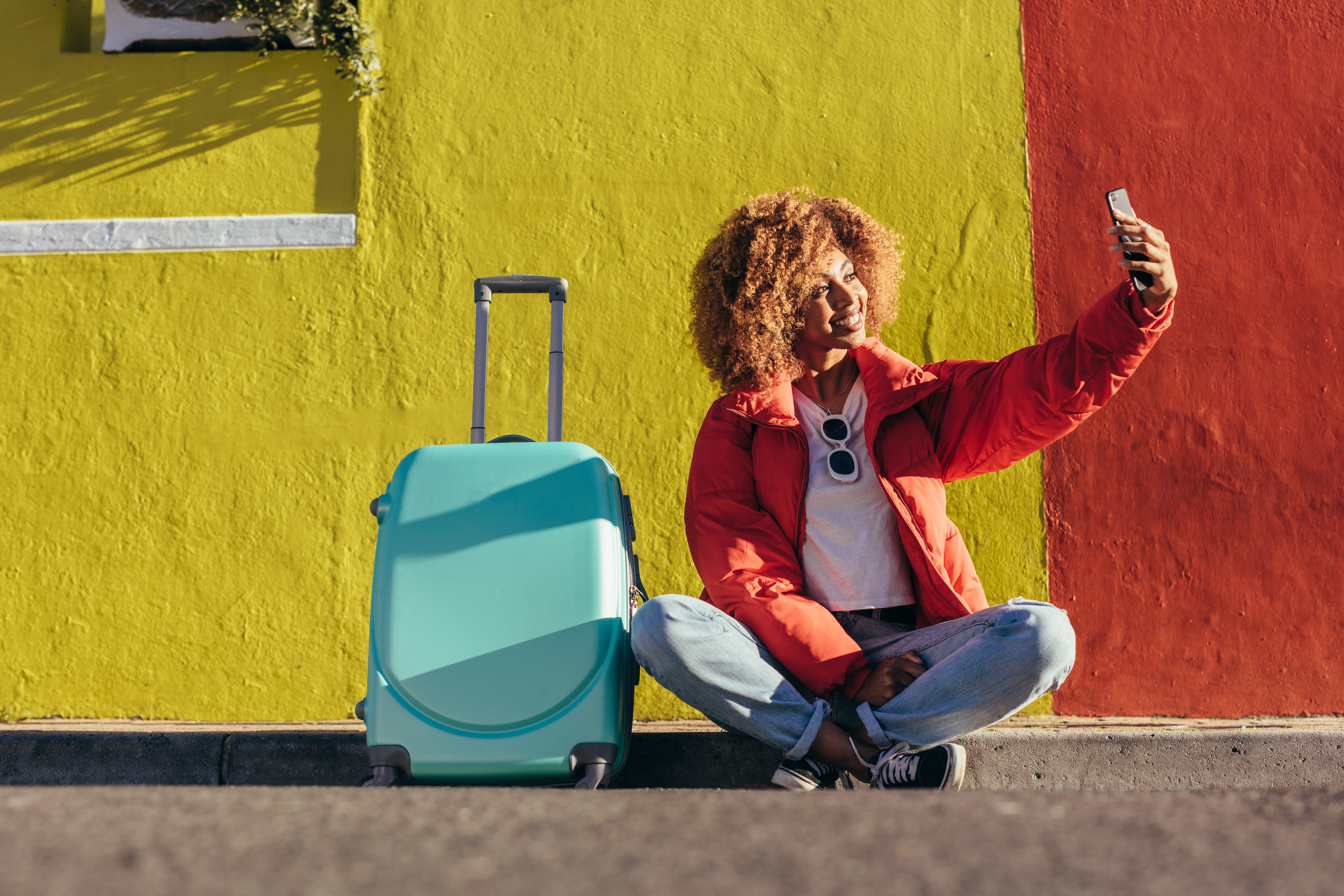 Woman taking selfie in front of a brightly colored wall next to a suitcase