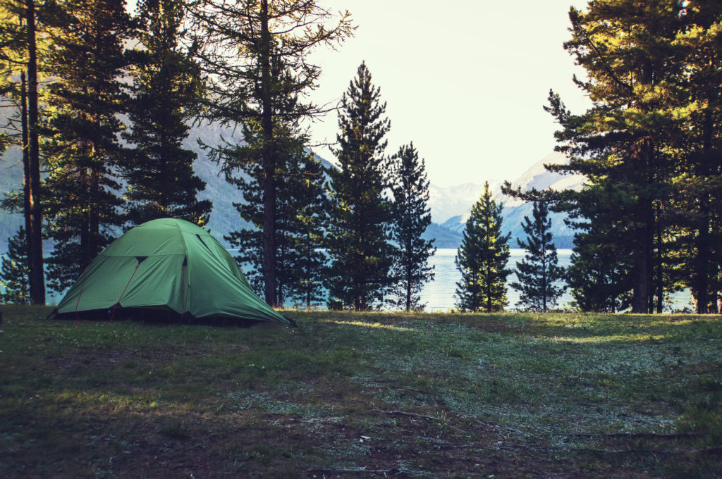 A tent in the woods overlooking a lake