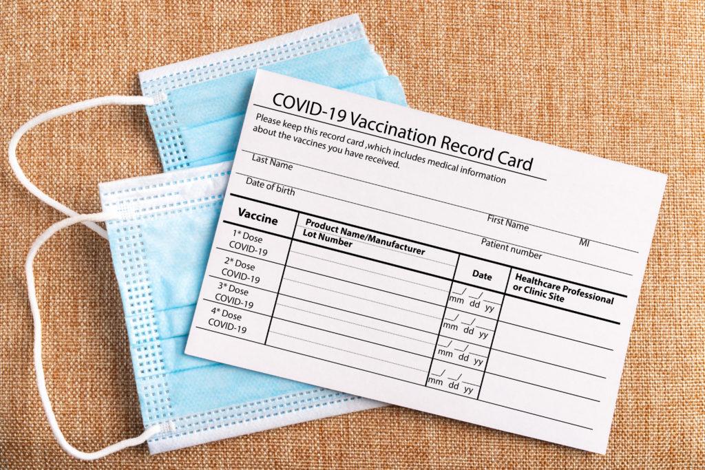 COVID-19 vaccination card and medical masks