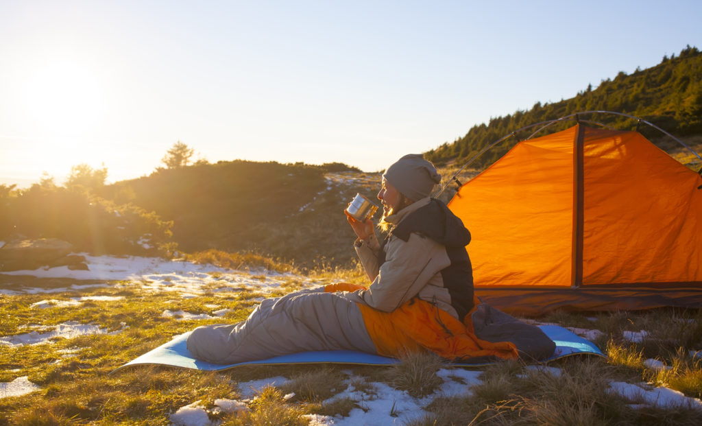 Woman drinking from a metal cup in a sleeping bag