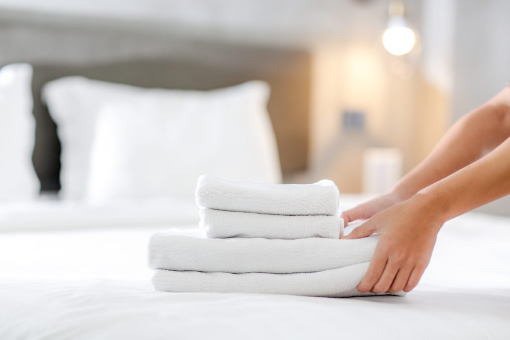 Person placing folded white sheets on white bed