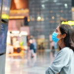 Woman in face mask looking at information board checking her flight in international airport