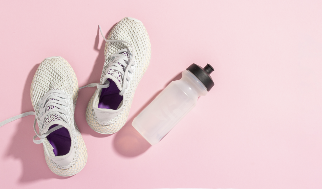 Sneakers and a water bottle on a pink background