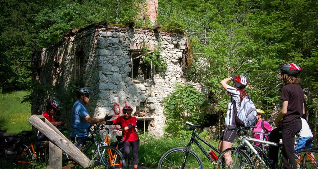 People on bikes examining a crumbling stone house