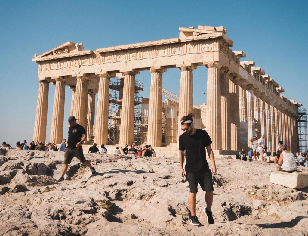 Men walking around Greek ruins