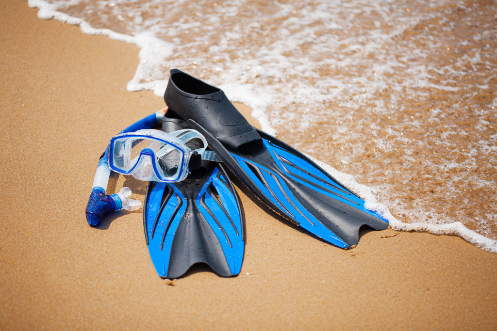 Blue flippers and snorkel mask at the beach