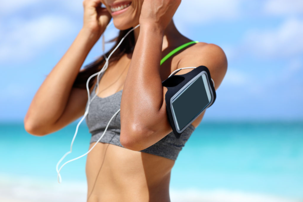Women wearing a smartphone fitness arm band on beach