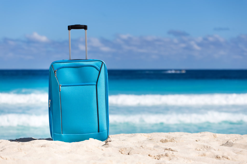 Blue suitcase on the sand in front of the ocean