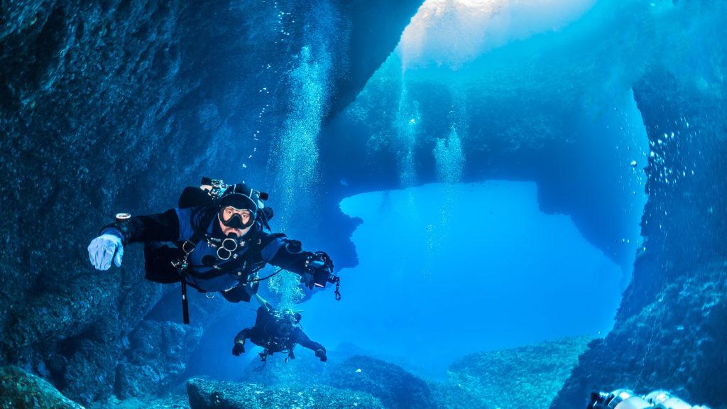 Two scuba divers diving near coast of Malta