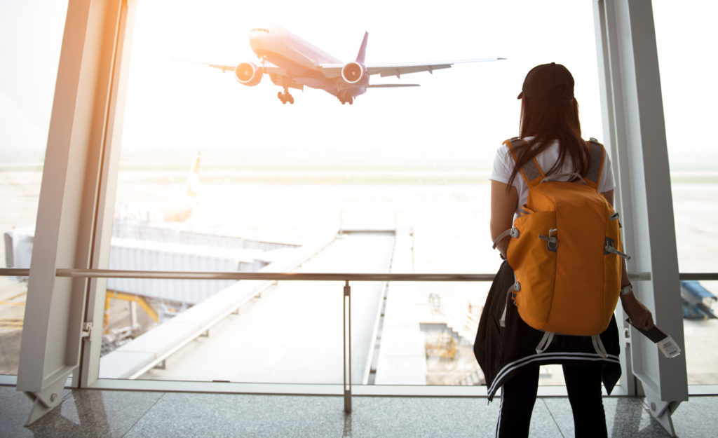 Women wearing yellow backpack and looking out of airport terminal window at an airplane