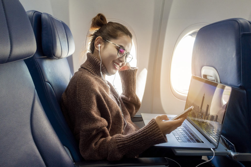Woman using laptop and phone on flight
