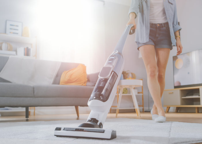 Woman vacuuming with a cordless vacuum