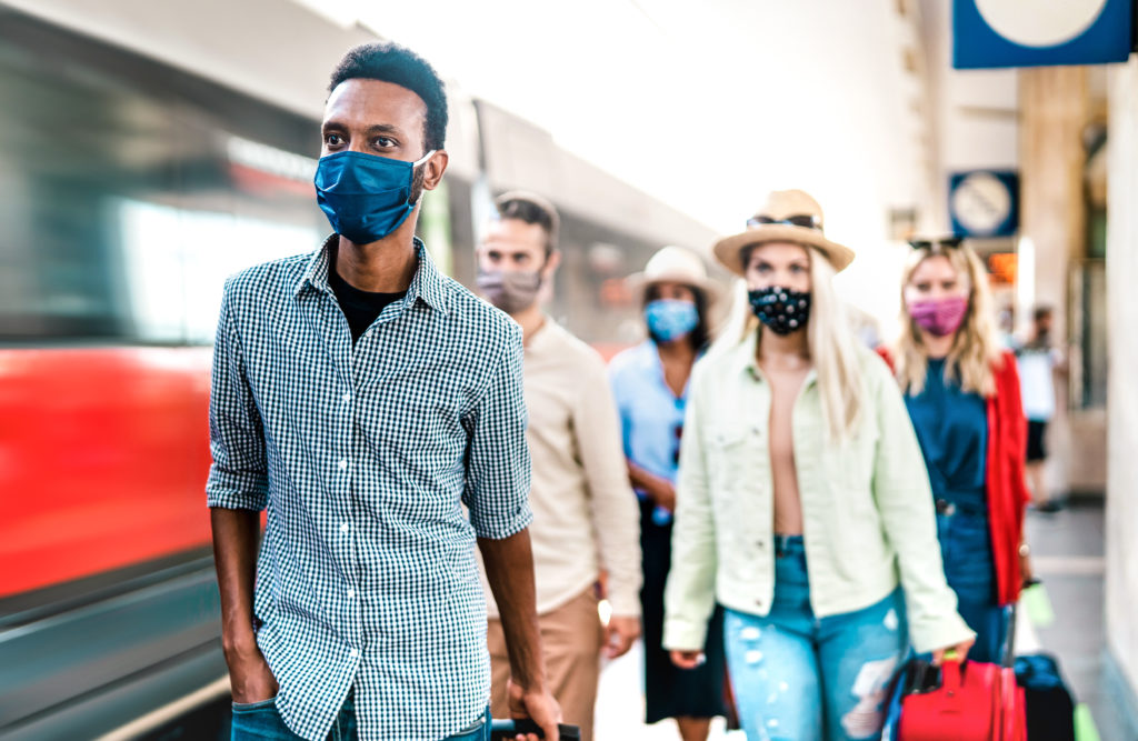 Group wearing face masks exits train