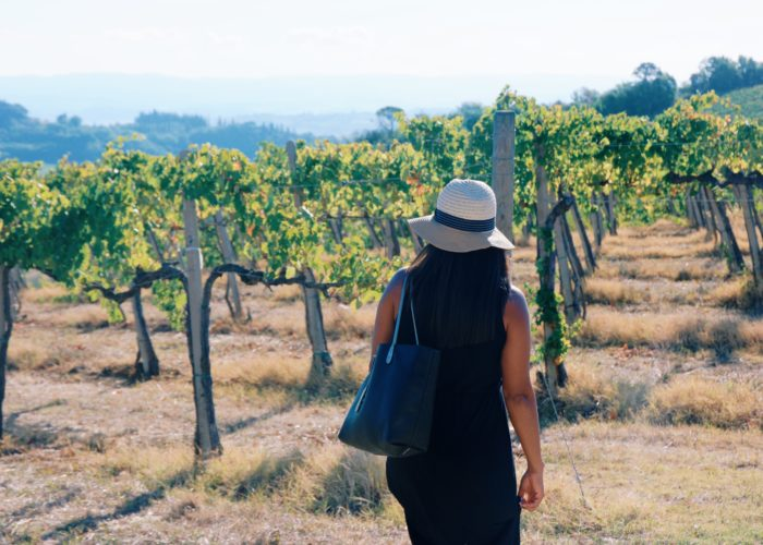 Woman walking through vineyard in Tuscany, Italy