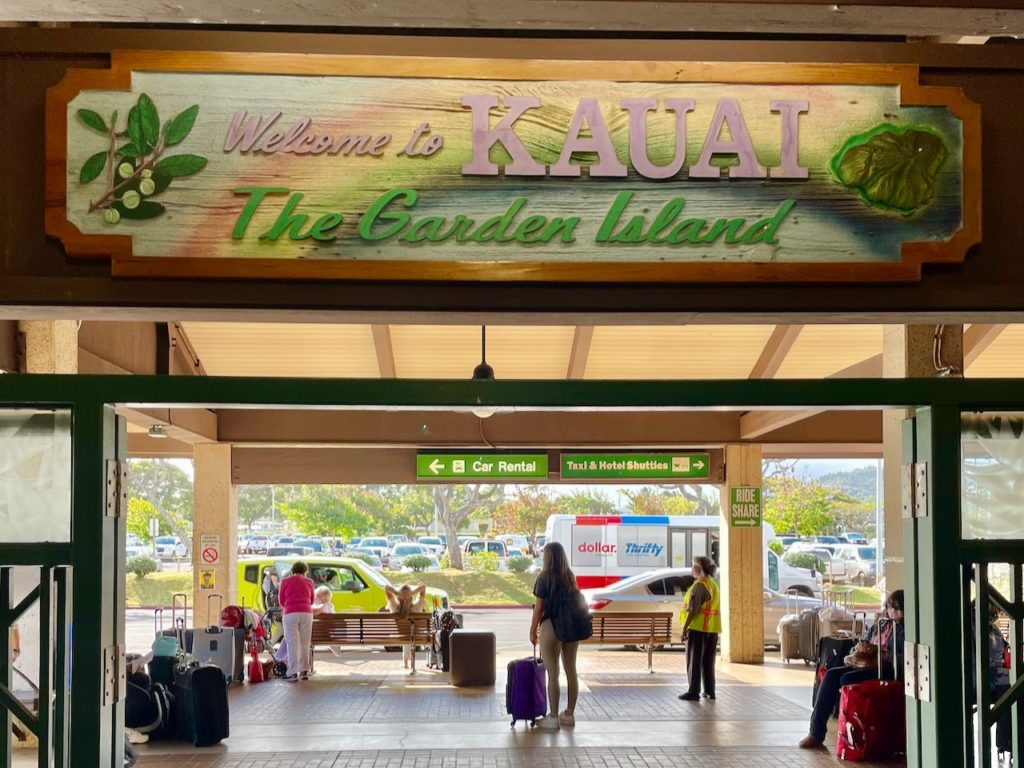 """Tourists with suitcases waiting beneath a """"Welcome to Kauai"""" sign"""