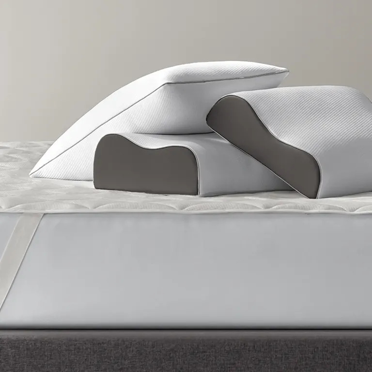 Three Sleep Number True Temp Ultimate Pillows stacked on top of a mattress