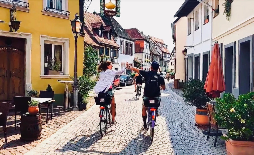 Two people high-fiving on bikes on a cobblestone street