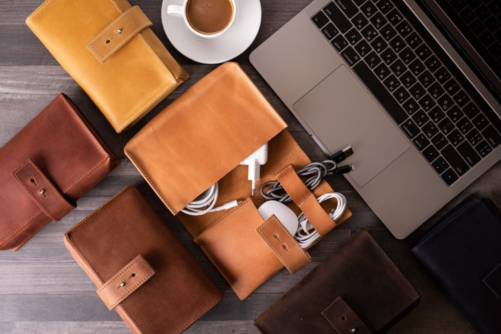 Multiple leather cable organizers on a table around a laptop