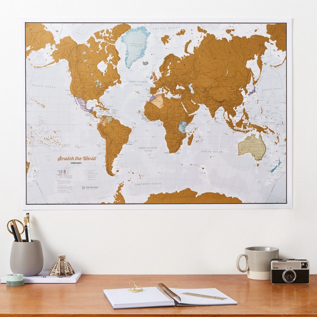 Scratch-off world map hanging on wall above a desk