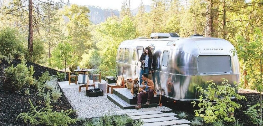 Two people and a dog sitting on the small deck outside an airstream at AutoCamp Yosemite