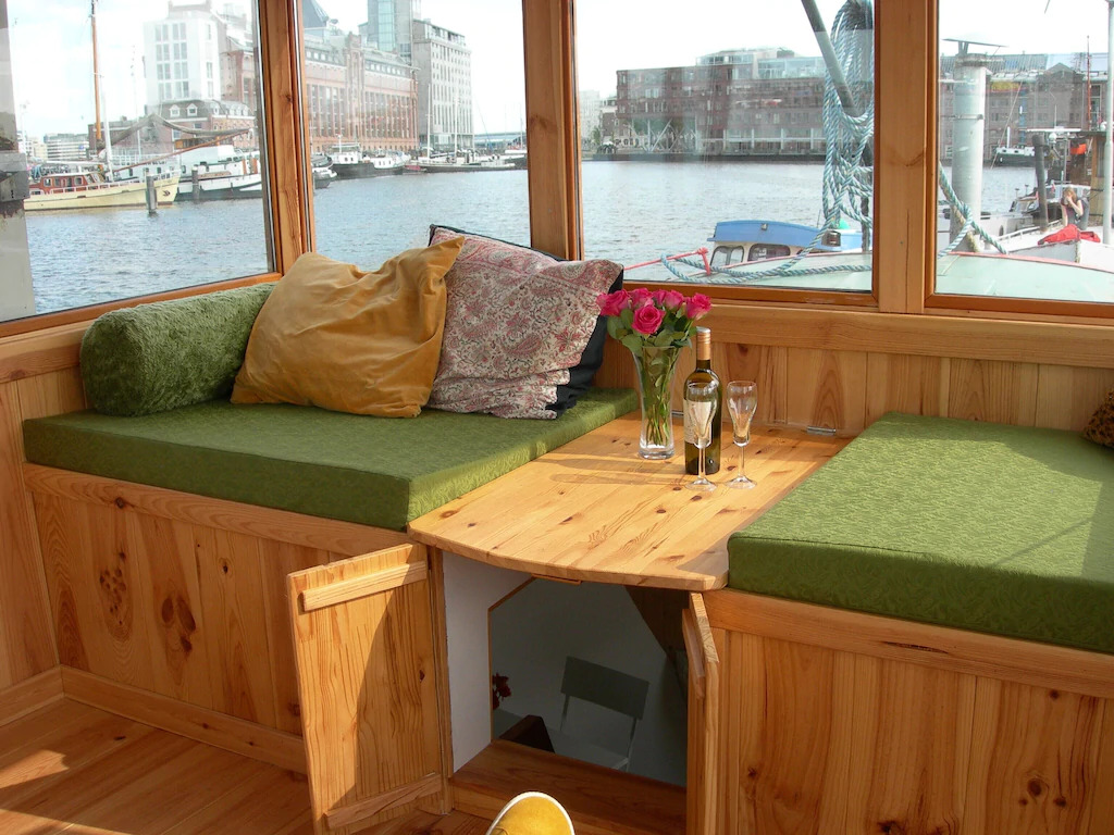 A wooden sitting area arranged with a bottle of wine and two glasses, overlooking a marina in Amsterdam, Netherlands