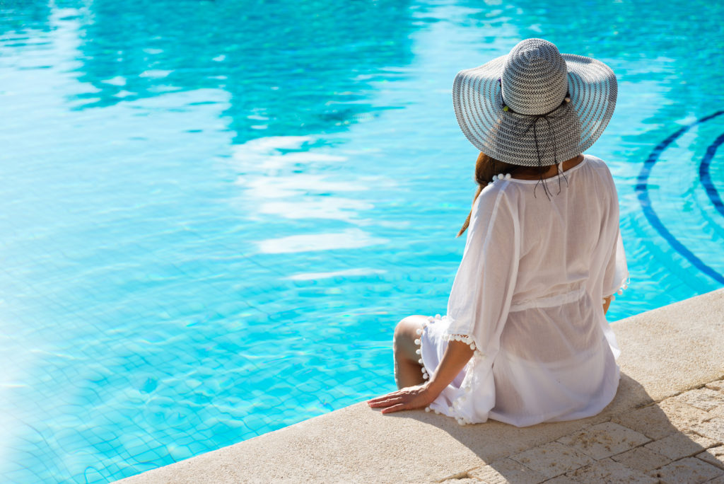 A woman facing away from the camera in a white swimsuit cover up and hat looking out over a resort pool