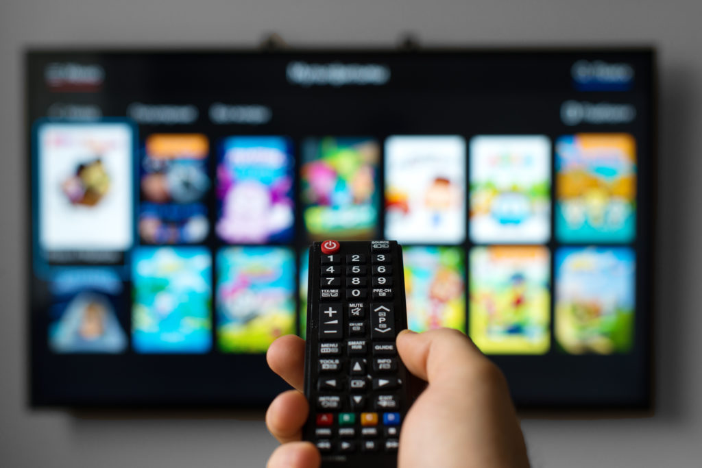 Hand holding TV remote with TV in background